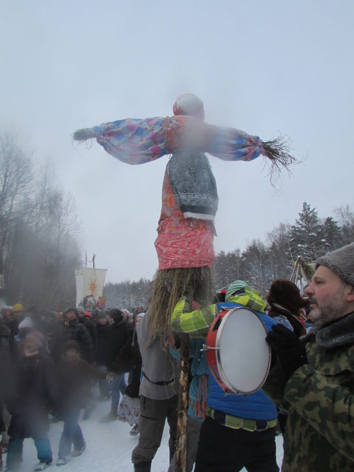 Straw effigy of a woman in traditional dress surrounded by a crowd
