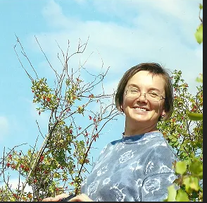 head shot of woman, trees in background