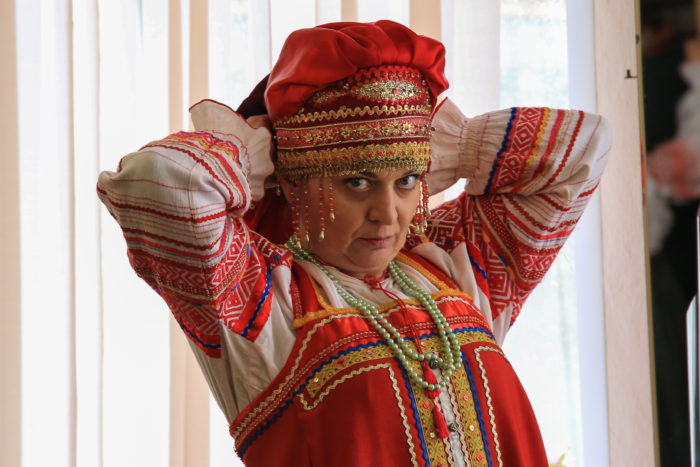 woman in Russian folk dress adjusts her headgear